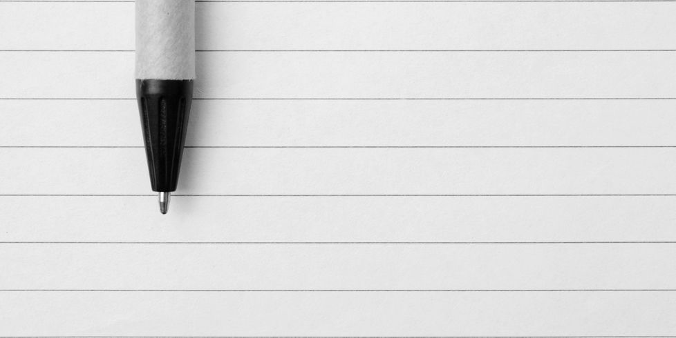 a pen resting on lined paper