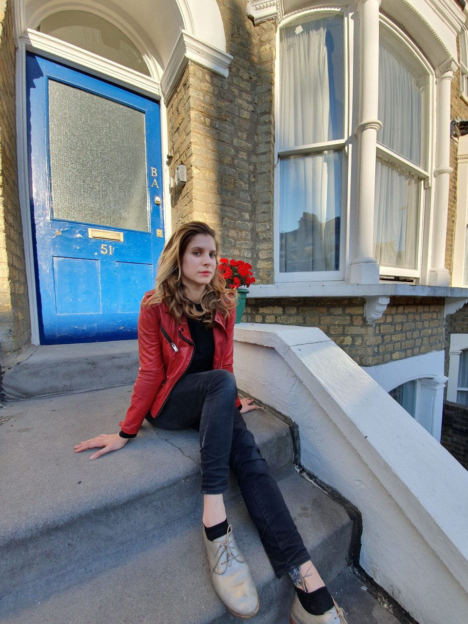 a woman sat on steps outside a blue door
