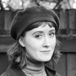 a person with a long bob wearing a beret