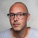 a person with a bald head and tortoishell glasses