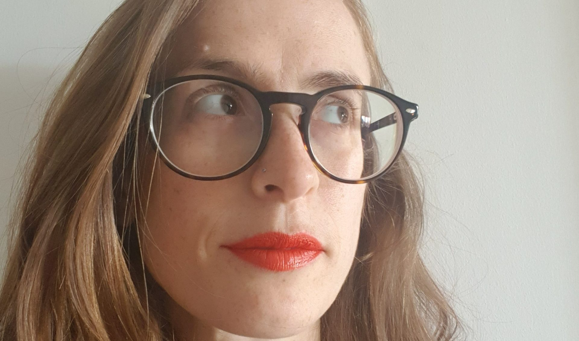 a person with long hair, red lipstick and glasses looking up