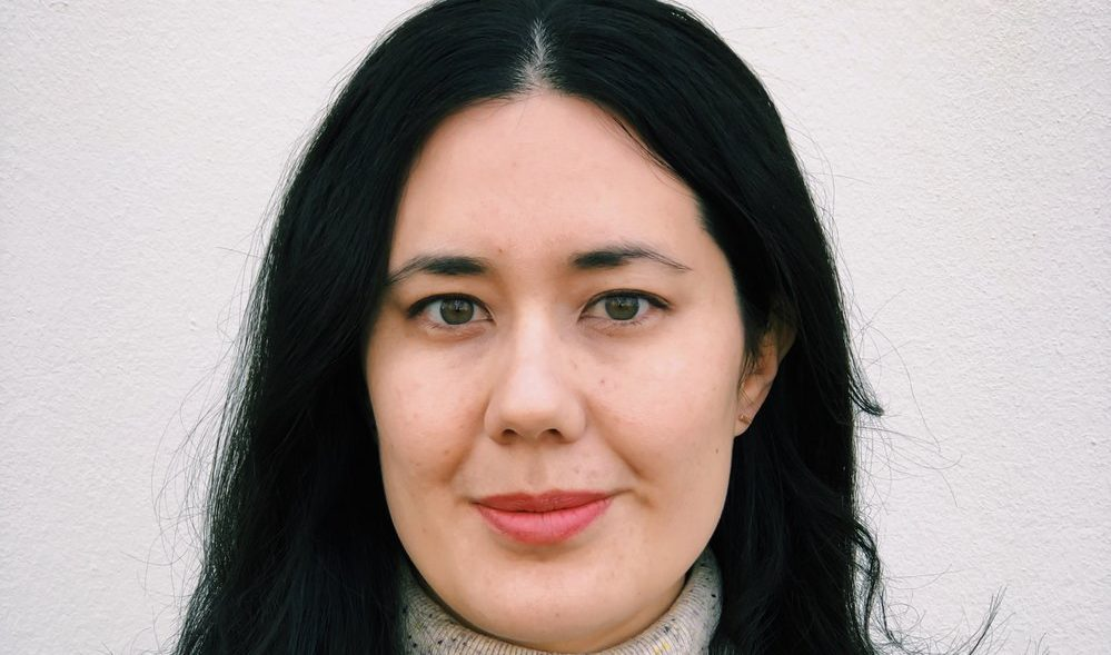 photo of a person with long black hair and a white/cream jumper