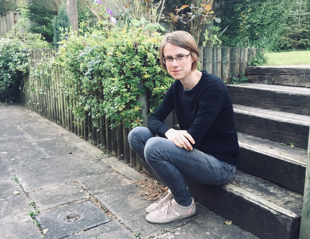 A woman with short dark blonde hair wearing glasses, a blue jumper and blue jeans sitting on some steps looking at the camera.
