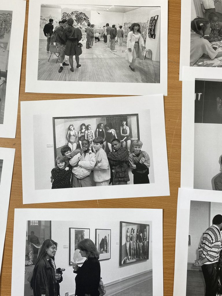 a photo of three black and white photos of people chatting and interacting in an art gallery